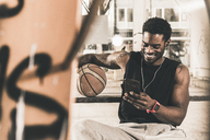 Smiling man with tattoos and basketball using smartphone and earphones - UUF12978