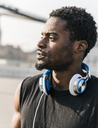Portrait of young man with headphones outdoors - UUF13014