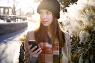 Woman smart phone looking away while standing - CAVF05602