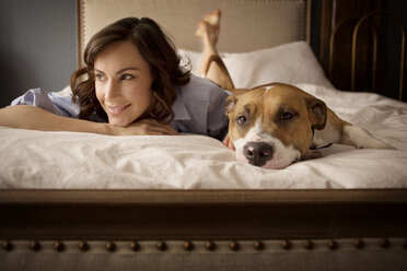 Woman looking away while relaxing with dog on bed at home - CAVF05620