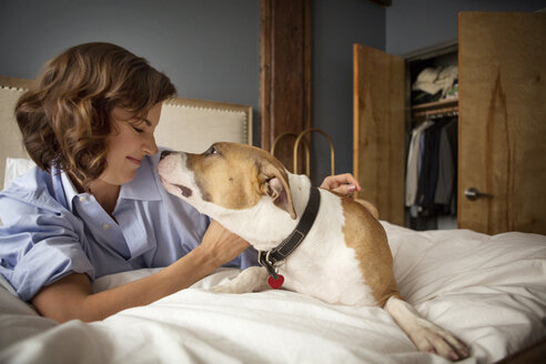 Smiling woman playing with dog on bed at home - CAVF05623