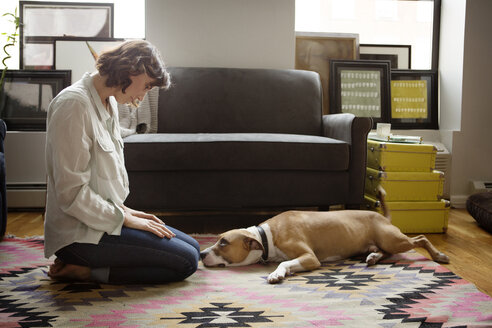 Woman looking at dog lying on carpet - CAVF05626