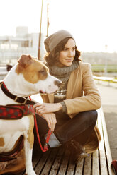 Woman with dog looking away while sitting on bench - CAVF05632