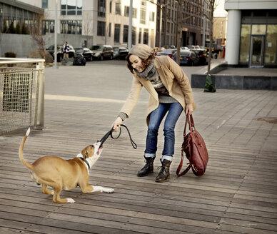 Dog on woman pulling pet leash on footpath in city - CAVF05635