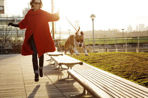 Woman running with dog jumping on benches at park - CAVF05638