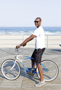 Man with bicycle standing on pier against beach - CAVF05866