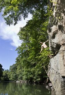 Man standing on cliff against lake - CAVF05899