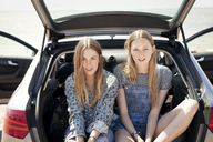 Portrait of women sitting in car trunk - CAVF05983
