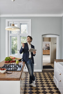 Man using tablet in kitchen looking at ceiling lamp - RORF01125