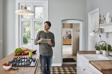 Man using tablet in kitchen looking at ceiling lamp - RORF01128