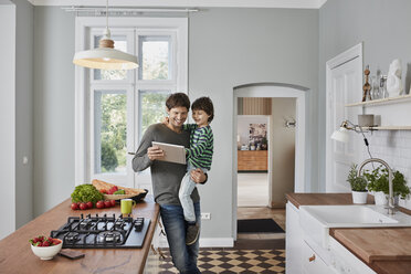 Happy father and son using tablet in kitchen together - RORF01131