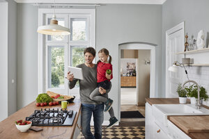 Happy father and daughter with bell pepper and tablet in kitchen - RORF01134