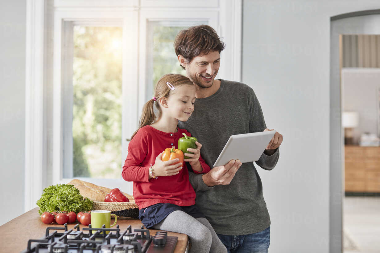 Smiling father and daughter with bell pepper and tablet in kitchen - RORF01137 - Roger Richter/Westend61