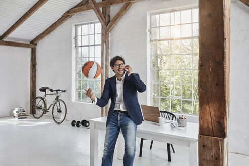 Laughing businessman with basketball on cell phone in penthouse - RORF01143