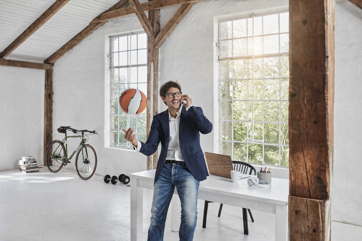 Laughing businessman with basketball on cell phone in penthouse - RORF01143 - Roger Richter/Westend61
