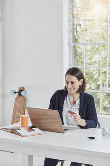 Happy businesswoman using laptop on desk holding card - RORF01152