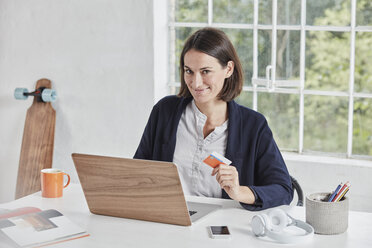 Portrait of smiling businesswoman with laptop on desk holding card - RORF01158