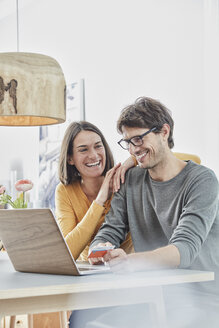 Happy couple with a card using laptop on table at home - RORF01167