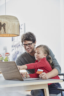 Happy father and daughter with a card using laptop on table at home - RORF01170