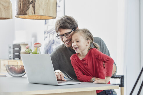 Happy father and daughter using laptop on table at home - RORF01173