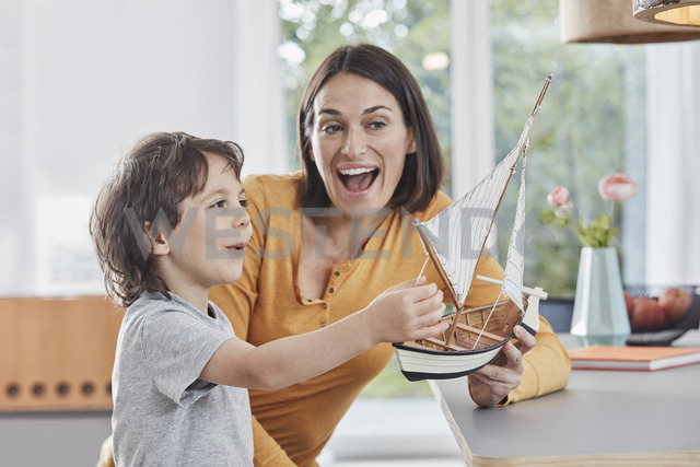Happy mother and son playing with model boat at home - RORF01176