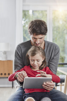Father and daughter using tablet at home together - RORF01179