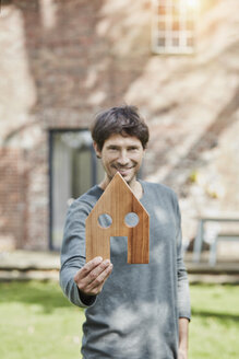 Portrait of smiling man in front of his home holding house model - RORF01197