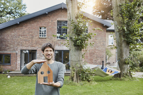 Portrait of man in garden of his home holding house model with woman in background lying in hammock - RORF01200