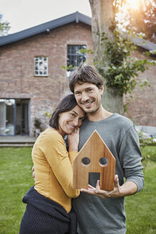 Portrait of smiling couple in garden of their home holding house model - RORF01203