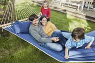 Happy family playing in hammock in garden of their home - RORF01215