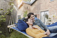 Happy couple lying in hammock in garden of their home - RORF01218