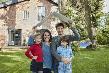 Portrait of happy family in garden of their home holding roof - RORF01230