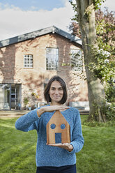 Portrait of smiling woman in garden of her home holding house model - RORF01236