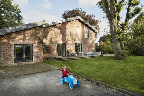 Girl playing with soapbox in driveway of residential house - RORF01239