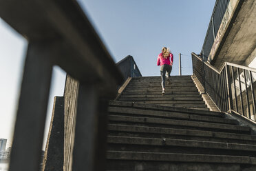 Young woman running up stairs - UUF13055