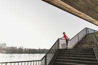 Young woman stretching on stairs at a river in the city - UUF13058