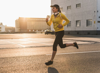 Young woman running on a street at  sunset - UUF13073