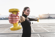 Young woman exercising in the city at sunet - UUF13076