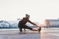 Young woman stretching at the riverside in the city at sunset - UUF13082