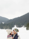 Happy couple face to face in snowy field - CAIF12348
