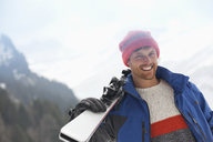 Portrait of smiling man holding skis - CAIF12351