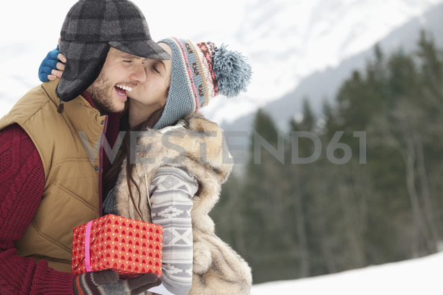 Happy couple with Christmas gift kissing in snowy field - CAIF12360