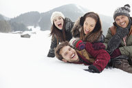 Playful friends laying in snowy field - CAIF12366