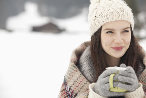 Close up of smiling woman in knit hat and gloves drinking coffee in snowy field - CAIF12369