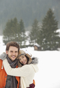 Portrait of smiling couple hugging in snowy field - CAIF12372