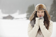 Portrait of smiling woman wearing fur hat and gloves in snowy field - CAIF12375