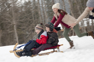Enthusiastic family sledding in snowy field - CAIF12390