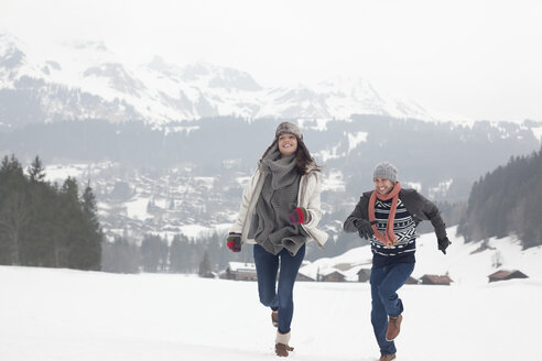 Happy couple running in snowy field - CAIF12393