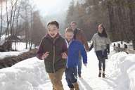 Happy family running in snowy lane - CAIF12396