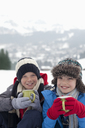 Portrait of smiling boys drinking hot chocolate in snowy field - CAIF12408